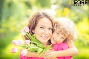 38259953 - mother and daughter with bouquet of flowers against green blurred background. spring family holiday concept. mother's day